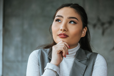 pensive young asian woman holding hand on chin and looking up in office