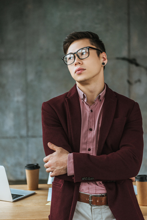 handsome young busienssman in eyeglasses standing with crossed arms and looking away in office Stok Fotoğraf