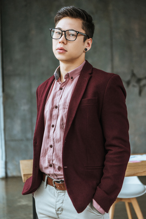 handsome young man in eyeglasses standing with hands in pockets and looking at camera in office Stok Fotoğraf