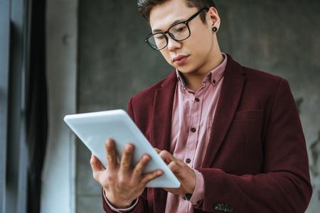 focused young man in eyeglasses using digital tablet in office Stok Fotoğraf
