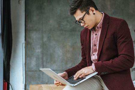 handsome young businessman in eyeglasses sitting and using laptop in office Stok Fotoğraf