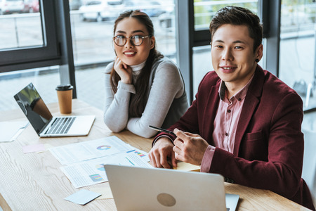 happy young asian business people working with laptops and smiling at camera in office Stok Fotoğraf - 116324132