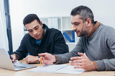 collègues masculins concentrés travaillant avec des papiers et un ordinateur portable au bureau
