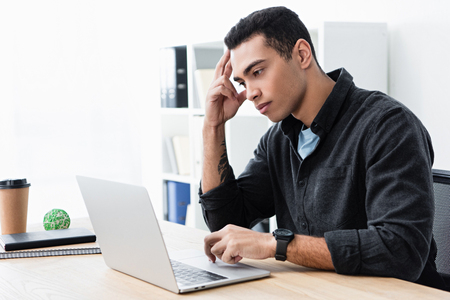 serious concentrated young businessman working with laptop in office Stock fotó