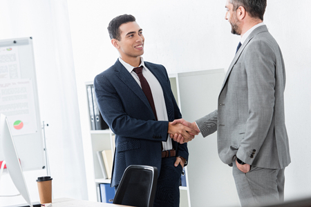 professional businessman in formal wear shaking hands and smiling each other in office Imagens