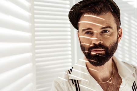 handsome bearded man in cap near white room divider Фото со стока