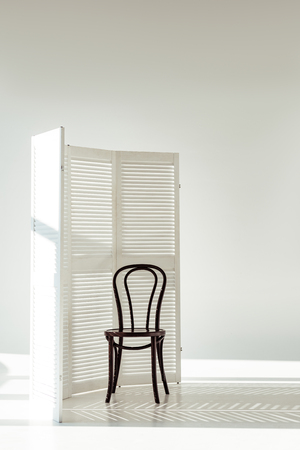 dark wooden chair and white room divider with shadows and sunlight Фото со стока - 116323274