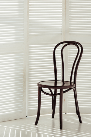 black wooden chair and white room divider with shadows 写真素材 - 116323276