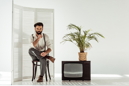 handsome bearded man sitting on chair near folding screen and tv in white room Banco de Imagens