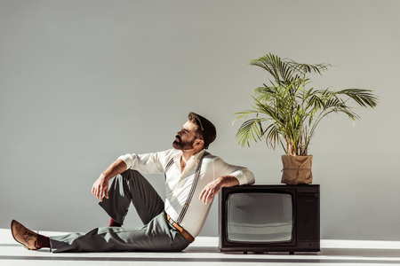 handsome bearded man sitting on floor near vintage tv with plant in pot