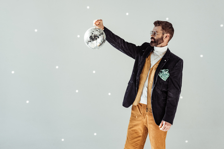 handsome bearded man looking at disco ball in hand on grey background