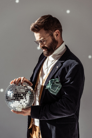 handsome bearded man in glasses holding disco ball on grey background