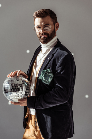 handsome man in glasses holding disco ball and looking at camera on grey background