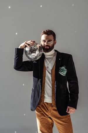 handsome bearded man in glasses holding disco ball on shoulder and looking at camera on grey background