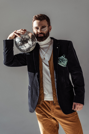 bearded man holding disco ball on shoulder and looking at camera isolated on grey
