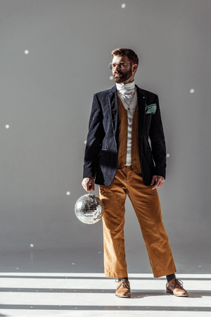 handsome man holding disco ball and posing on grey background