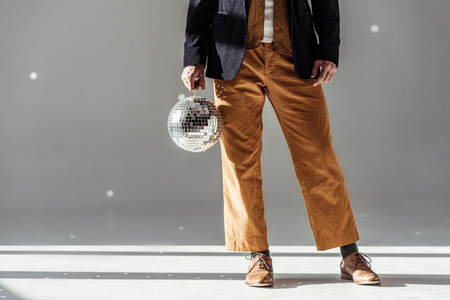 cropped view of man holding mirror ball on grey background