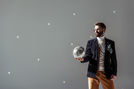 bearded man looking at mosaic disco ball in hand on grey background