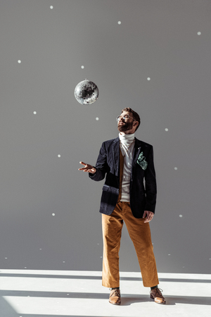 handsome man in glasses high throwing up disco ball on grey background