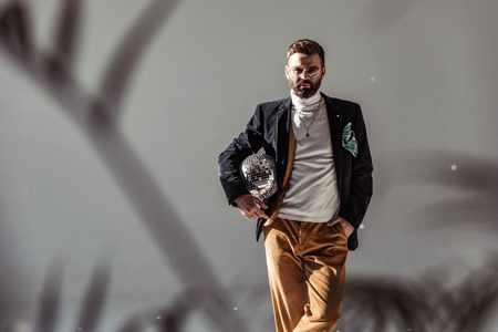 selective focus of bearded man holding mosaic disco ball and looking at camera on grey background Stock Photo