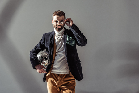 bearded man touching glasses, holding mosaic disco ball and looking at camera on grey background Stock Photo