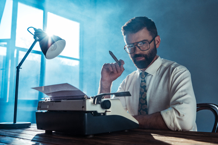 bearded journalist in glasses sitting at table with vintage typewriter, holding cigar and looking at camera near window
