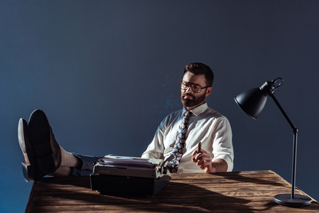 bearded journalist putting feet up on table, looking at vintage typewriter and holding cigar on grey background Standard-Bild - 116322884
