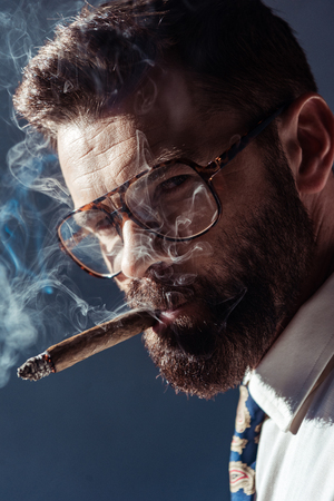 handsome bearded man in glasses smoking and looking at camera