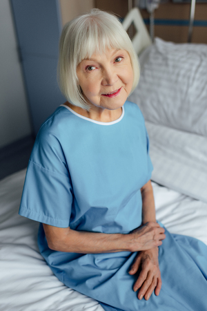 smiling senior woman with folded hands sitting on bed and looking at camera in hospital
