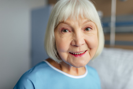 portrait of happy senior woman with grey hair looking at camera in hospital