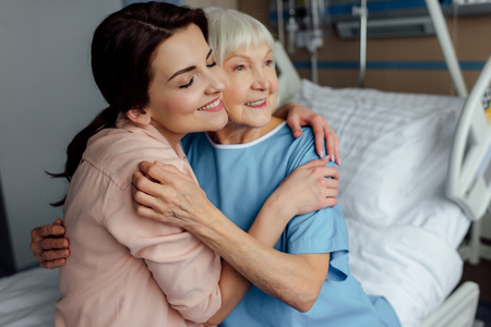 smiling senior woman and daughter sitting on bed and embracing in hospital
