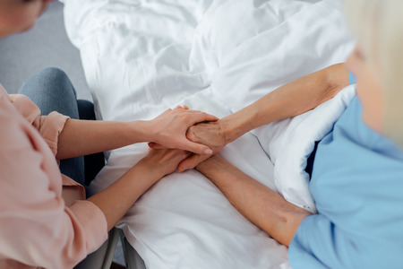 cropped view of senior woman and daughter holding hands in hospital