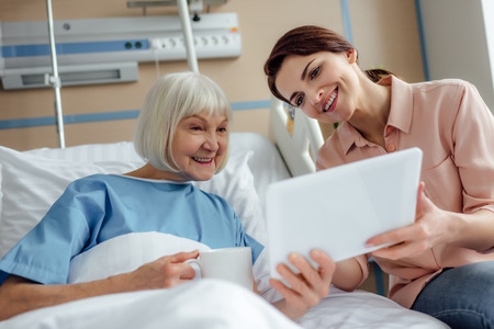 happy senior woman and daughter using digital tablet in hospital bed