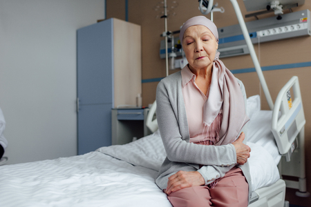 senior woman with cancer sitting on bed in hospital with hands crossed
