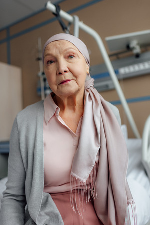 senior woman in kerchief with cancer sitting on bed in hospital and looking at camera Stok Fotoğraf - 116322570