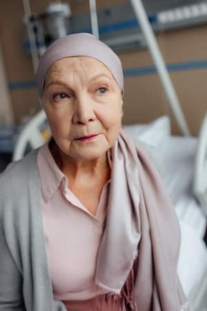 sad senior woman with cancer sitting on bed in hospital and looking away