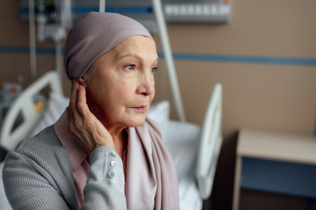 upset senior woman with cancer sitting on bed in hospital Stok Fotoğraf