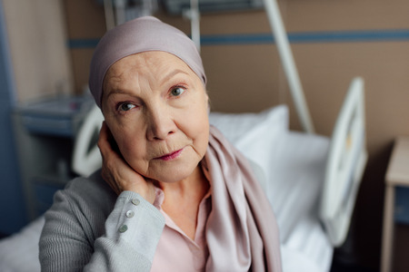 upset senior woman with cancer sitting on bed in hospital and looking at camera Stok Fotoğraf