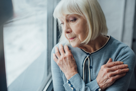 sad senior woman with hands crossed near window at home