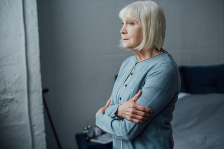pensive senior woman in casual sweater with arms crossed at home