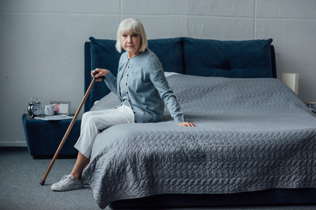 senior woman sitting on bed with walking stick at home and looking at camera Foto de archivo