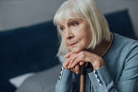 portrait of thoughtful senior woman with hands on walking stick sitting on bed at home Stock Photo