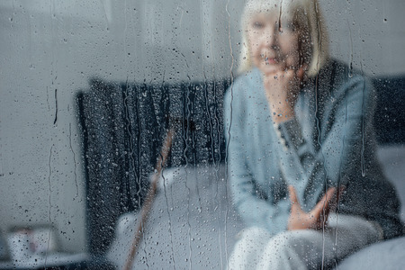 lonely senior woman sitting on bed and propping chin with hand at home through window with raindrops