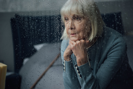 upset senior woman sitting and propping chin with hands at home through window with raindrops