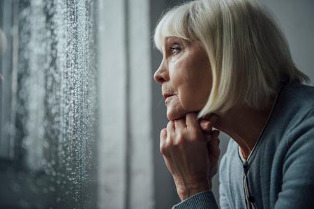 Mujer mayor con cabello gris apoyando la barbilla con la mano y mirando a través de la ventana con gotas de lluvia en casa