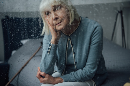 sad senior woman sitting on bed at home through window with raindrops