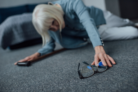 lonely senior woman lying on floor, feeling unwell and reaching for glasses at home