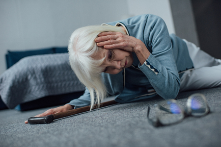 lonely senior woman lying on floor and having headache at home Banco de Imagens
