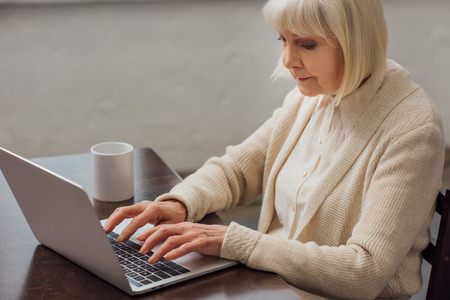 senior woman sitting at table and typing on laptop at home Фото со стока