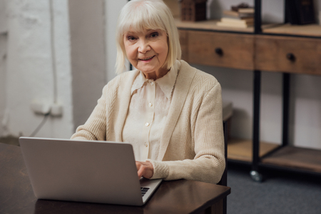 smiling senior woman sitting at table and typing on laptop at home Фото со стока